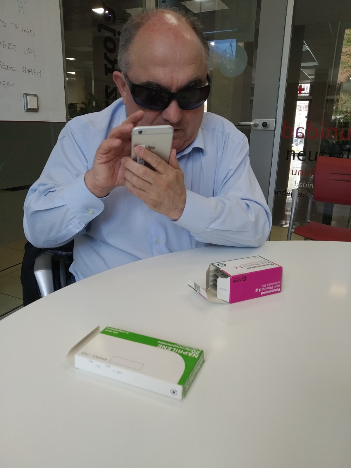 Andrés with the app in the smartphone and two containers of medications on the table